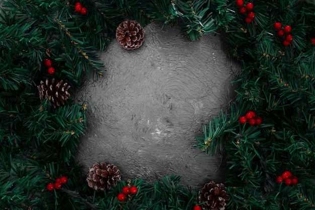 Christmas pine leaves frame on a grunge gray background Free Photo