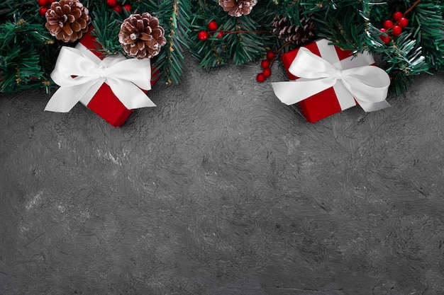 Christmas pine leaves with red boxes on a grunge gray background Free Photo