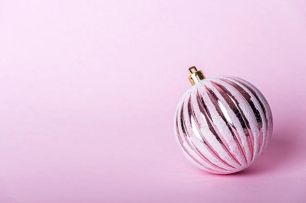 Рождественский розовый безделушка, блестящий шар на пастельном фоне. Premium Фотографии