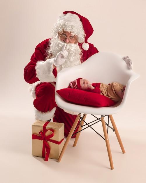 Ritratto di natale della piccola neonata sveglia, vestita in abiti natalizi e uomo che indossa cappello e costume da babbo natale Foto Gratuite