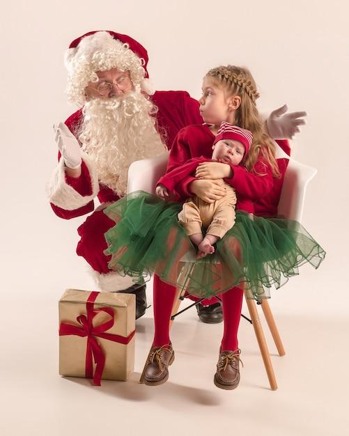 Ritratto di natale della piccola neonata sveglia e della sorella teenager graziosa vestita in abiti di natale e uomo che indossa il cappello e il costume della santa Foto Gratuite
