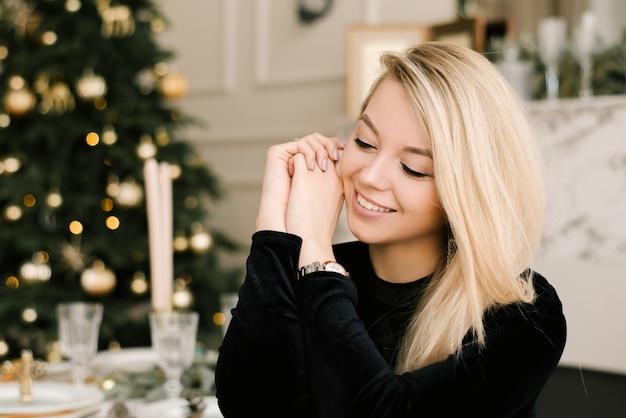 Рождественский портрет девушки в черном платье новогоднего декора Premium Фотографии