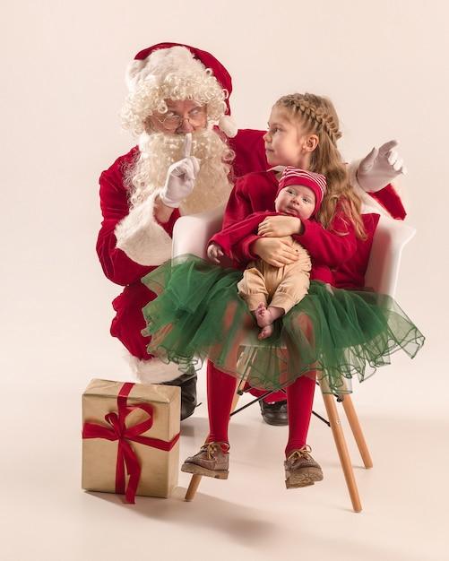 귀여운 신생아 아기 소녀, 예쁜 사춘기 자매의 크리스마스 초상화, 선물 상자 크리스마스 옷과 산타 클로스를 입고 무료 사진