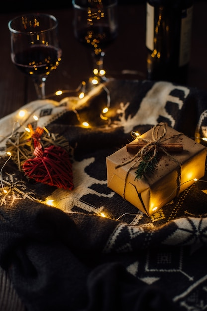 christmas present with knitted sweater christmas lights and two glasses of wine free photo