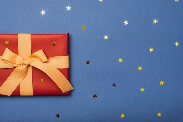 Christmas present with ribbon and golden stars Free Photo