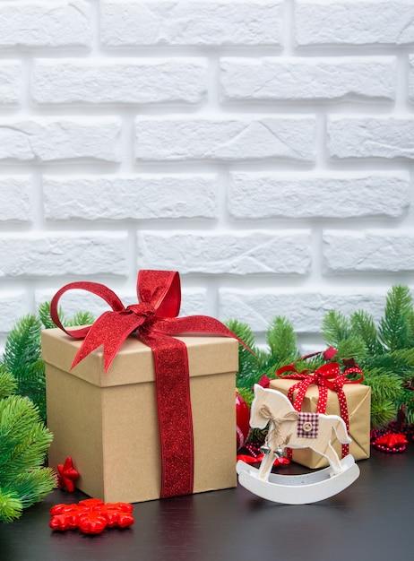Рождественские подарки в красных коробках на черном деревянном столе Premium Фотографии