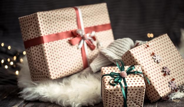Рождественские подарки над огнями на темной стене на уютном коврике. праздничные украшения Бесплатные Фотографии