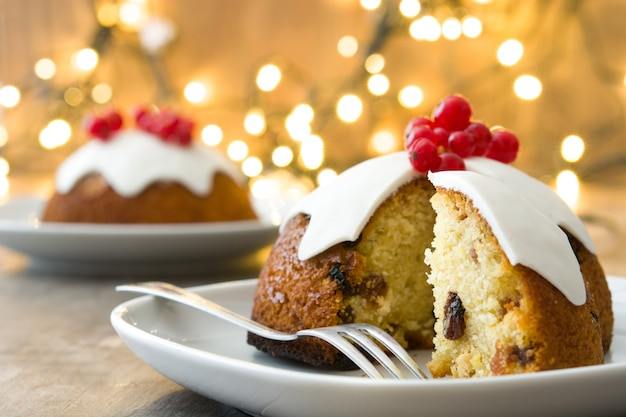 Christmas pudding on wooden table decorated with christmas light Premium Photo