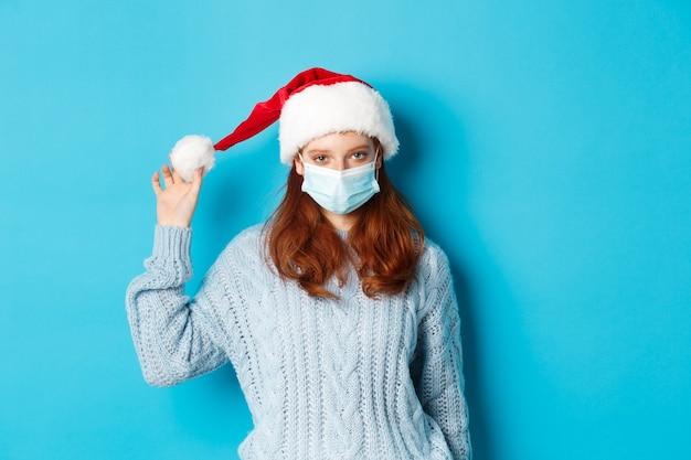 Рождество, карантин и концепция covid-19. рыжая девушка в маске для лица и играет в шляпе санта, празднует новый год в изоляции, стоя на синем фоне. Premium Фотографии