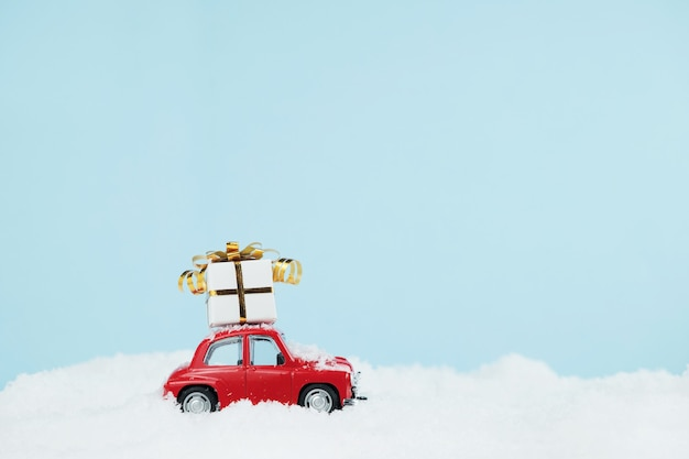 Christmas red car with a gift box in blue snowy landscape. happy new year card Premium Photo