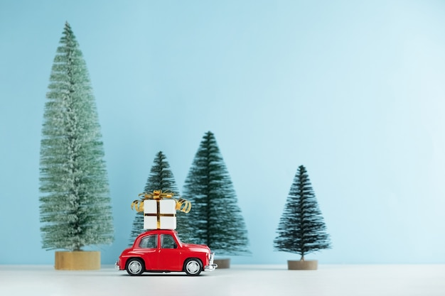 Christmas red car with a gift box in a pine forest.happy new year card Premium Photo