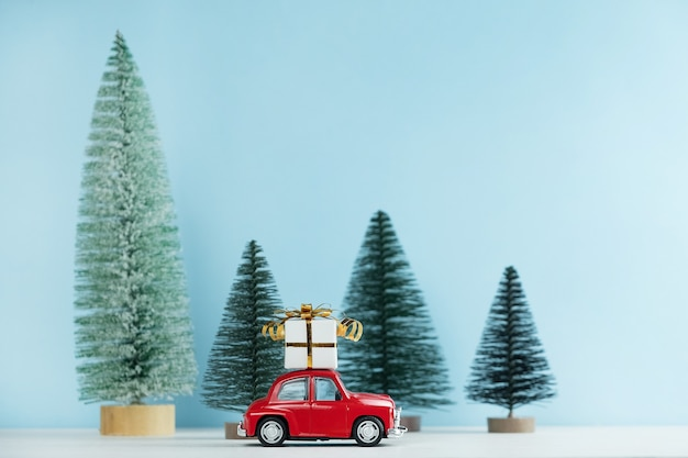 Christmas red car with a gift box in a pine forest. happy new year card Premium Photo