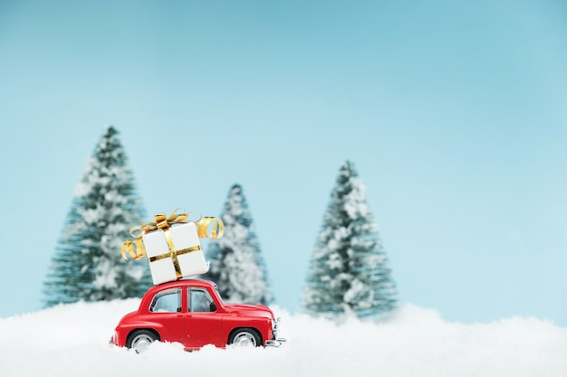 Christmas red car with a gift box in a snowy pine forest. happy new year card Premium Photo