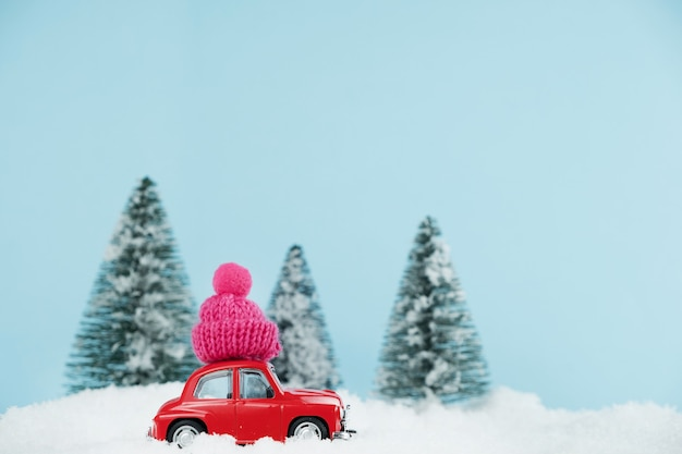Christmas red car with knitted pink hat in a snowy pine forest. happy new year card Premium Photo