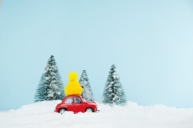 Christmas red car with knitted yellow hat in a snowy pine forest. happy new year card Premium Photo