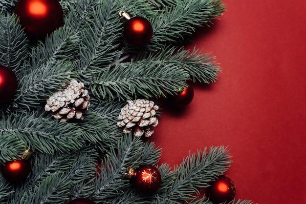 Рождественские красные украшения и еловые ветки Premium Фотографии