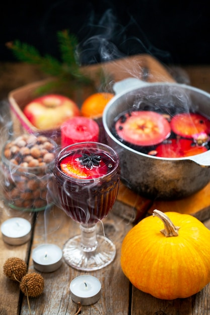 クリスマス赤ワインは、素朴な木製のテーブルの上のスパイスとフルーツのホットワインです。クリスマスの伝統的な温かい飲み物。柑橘系の果物、リンゴ、スパイスを鍋に入れたホットワイン。 Premium写真