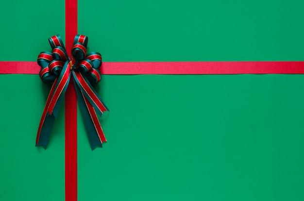 Рождественская лента с бантом на зеленом фоне. рождество и новый год концепция. Premium Фотографии