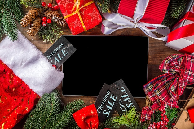 Christmas sale concept. black friday, green or cyber monday background with laptop, tablet, christmas decor and gift boxes Premium Photo