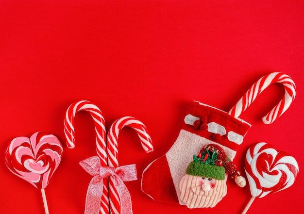 Рождественский санта-ботинок с конфетами на красном фоне Premium Фотографии