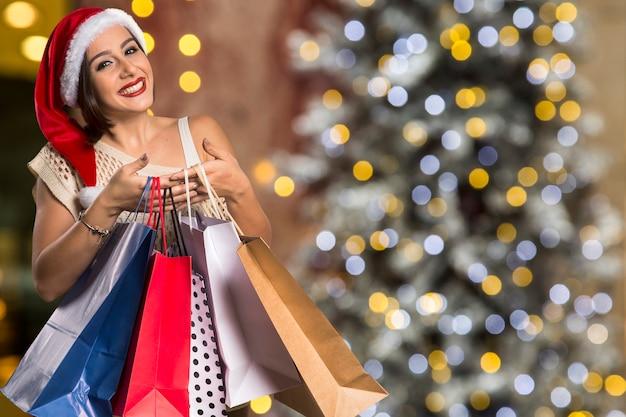크리스마스 산타 모자 고립 된 여자 초상화 개최 쇼핑 가방. 크리스마스 Bokeh 빛에 웃는 행복 한 여자 프리미엄 사진