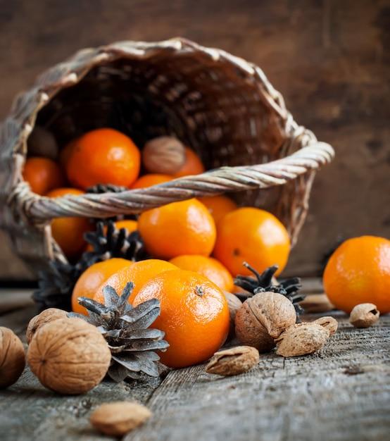 Christmas scene with tangerines, basket, nuts, pine cones Premium Photo