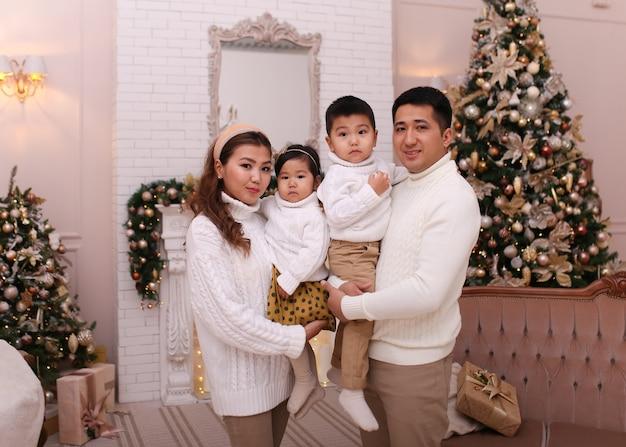 クリスマスの撮影のコンセプト、木で居心地の良いセーターで2人の子供と幸せなアジアの家族 Premium写真