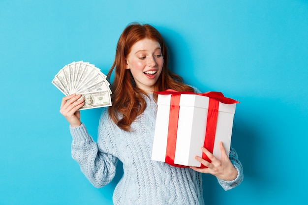 Christmas and shopping concept. cheerful girl with red hair, holding money and big new year gift, smiling happy, standing over blue background. Premium Photo