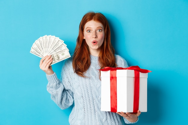 Christmas and shopping concept. excited redhead girl looking at camera, holding big new year gift and dollars, buying presents, standing over blue background. Premium Photo