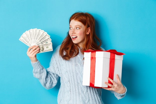 Christmas and shopping concept. excited redhead girl looking at dollars, holding big new year gift, buying presents, standing over blue background. Premium Photo