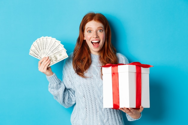 Christmas and shopping concept. happy redhead woman holding money and big xmas present, showing dollars and gift, smiling pleased, standing over blue background. Premium Photo