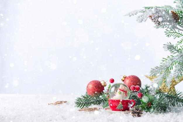 Рождественский снежный шар с сосновыми ветвями и праздничными украшениями на снежном столе. рождество или новый год концепция Premium Фотографии