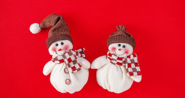 Рождественские игрушки снеговика на красном фоне Premium Фотографии