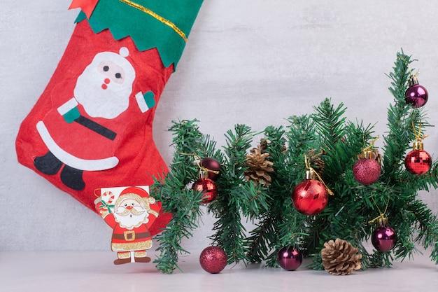흰색 표면에 축제 공 가득한 크리스마스 양말 무료 사진