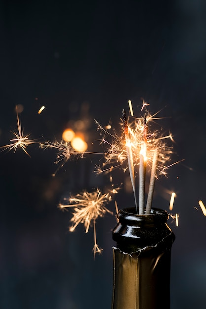 Christmas sparkler in champagne bottle at night Free Photo