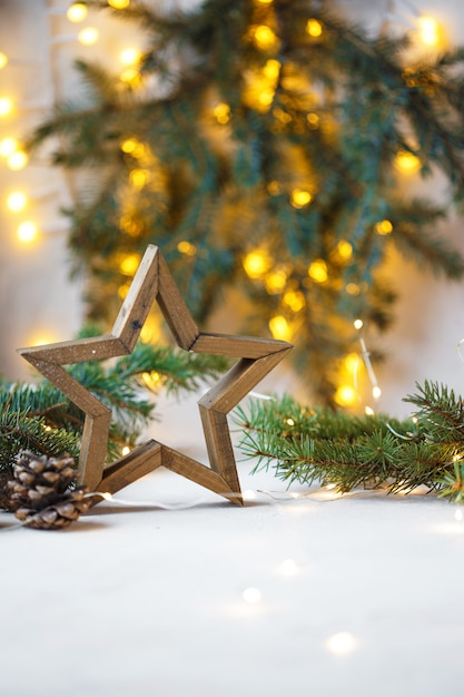 Christmas star, fir branches, new year decorations, notepad on light Premium Photo