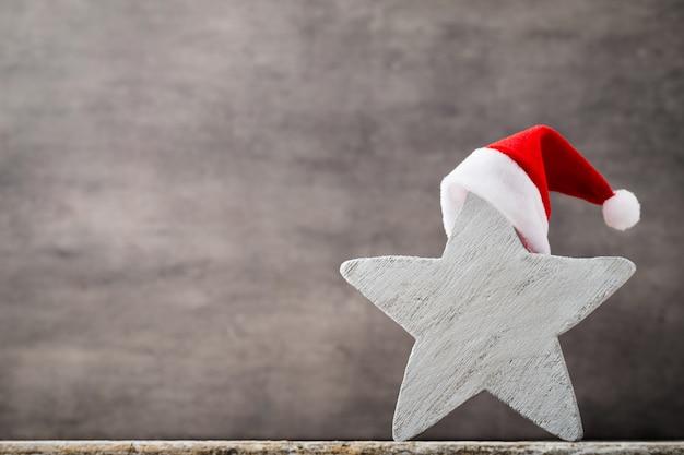 クリスマススターサンタ帽子。クリスマスのパターン。灰色の背景。 Premium写真