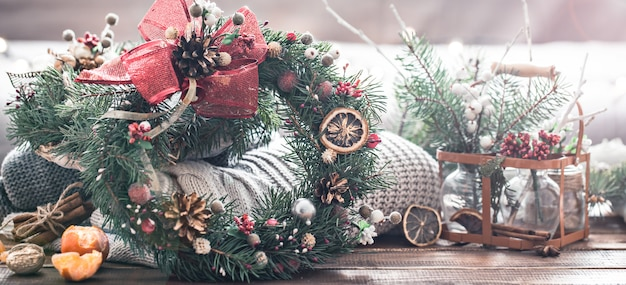 Christmas still life of a live christmas tree, decorations and festive wreath on a background of knitted clothes Free Photo