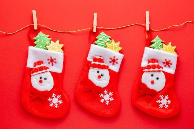 Рождественские чулки, полные имбирных пряников с глазурью на красном фоне Premium Фотографии