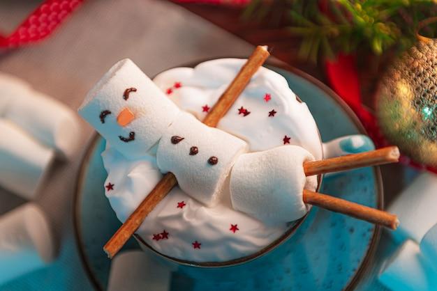 ココアとマグカップで横になっているマシュマロ男とクリスマスの表面、おもちゃ、花輪、ギフトのクリスマスツリーの表面 Premium写真
