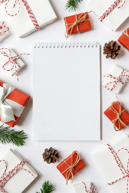 Поверхность рождества с пустой тетрадью, красными и белыми обернутыми подарочными коробками с лентой, еловыми ветками, шишками на белой поверхности. плоская планировка. место для текста. Premium Фотографии