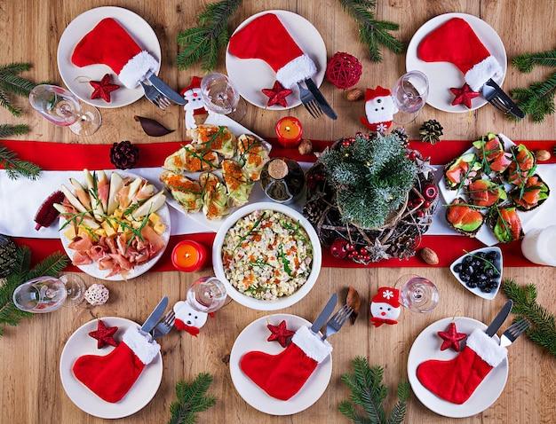 La tavola di natale viene servita con un antipasto, decorato con orpelli luminosi e candele. impostazione della tabella. cena di natale. lay piatto. vista dall'alto Foto Gratuite