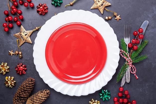 空の赤いプレート、石にお祝いデコレーション星の弓のボールが付いているカトラリーとクリスマステーブルの場所の設定 Premium写真