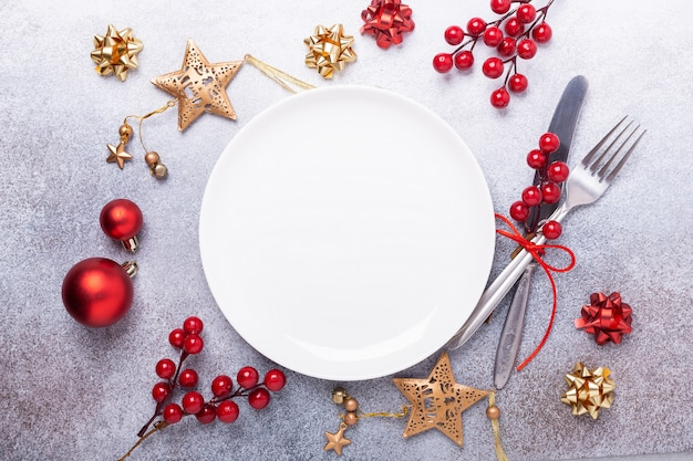 Christmas table place setting with empty white plate, cutlery with festive decorations on stone background Premium Photo