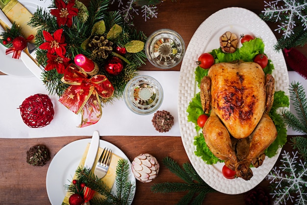 Christmas table served with a turkey, decorated with bright tinsel and candles Free Photo