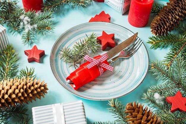 Сервировка стола рождества на голубой предпосылке с елкой и украшением. Premium Фотографии