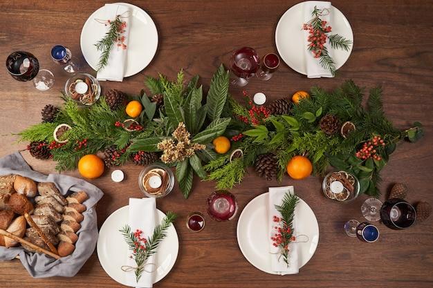 Сервировка рождественского стола с белыми пластинами и рождественской елкой на деревянном столе, вид сверху. Premium Фотографии