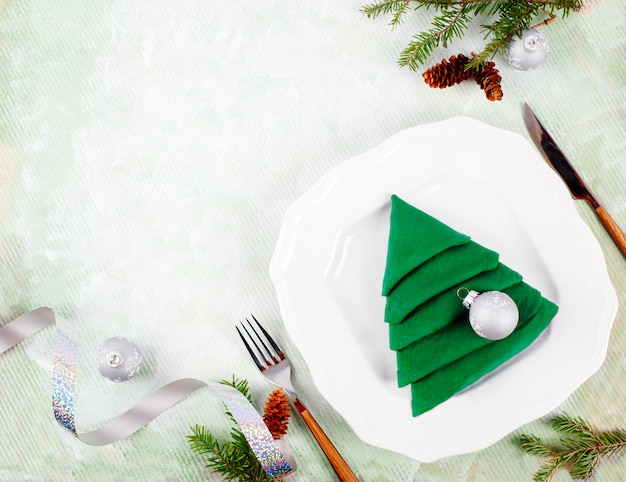 Christmas table setting with white plates and green christmas tree napkin fold on light green . top view, copyspace Premium Photo
