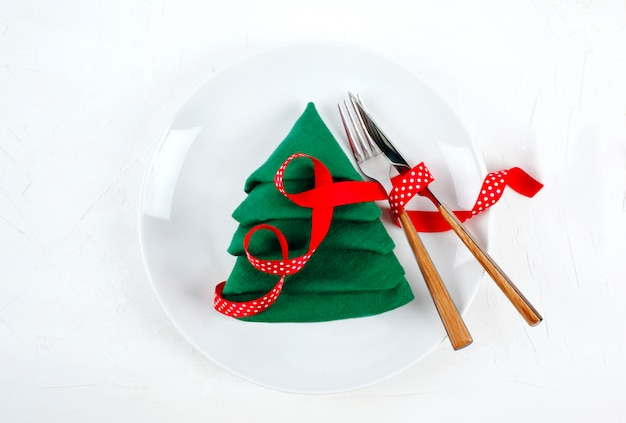 Christmas table setting with white plates and green christmas tree, top view napkin fold on white Premium Photo