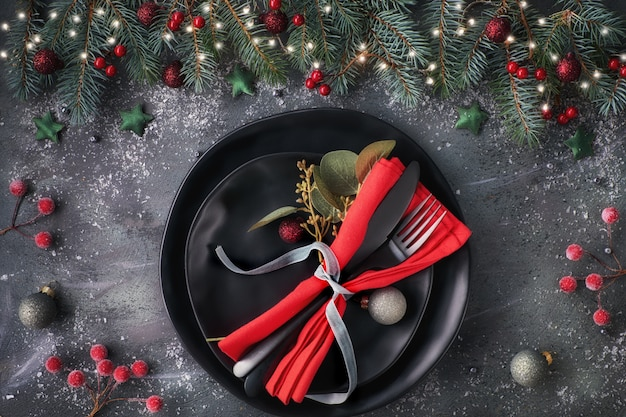 Christmas table setup on dark. flat lay with xmas decorations in green and red Premium Photo